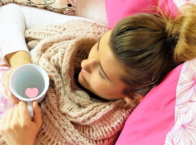 Lány egy pohárral az ágyban fekszik