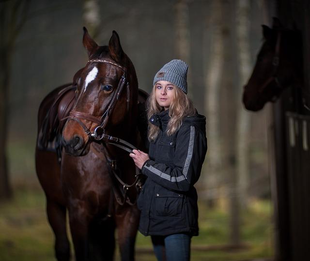 egy nő kantáron vezeti a lovat