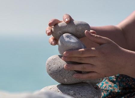 köveket egymásra helyező kezek