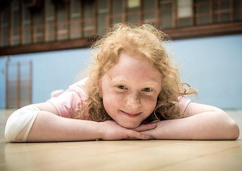 egy kiegyensúlyozott kislány a padlón fekve